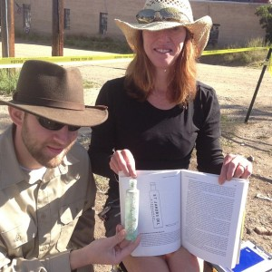 Jason holds up the bottle of St. James Oil uncovered at the site while Nancy Mahoney holds up the textbook the students read for the class illustrating the same bottle!